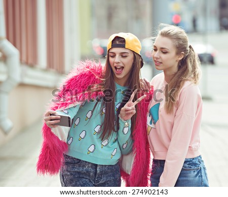 Fashionable beautiful young girlfriends walking together near a street road background. Two blonde and a brunette. Having funny and posing. outdoor. Toned in black and white retro style - stock photo