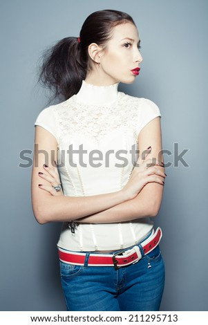 Fashionable beautiful young woman in trendy clothing (white waistcoat, blue jeans, red belt) posing over blue background. Silver accessories. Perfect skin. Horsetail hairdo. Hipster style. Studio shot - stock photo