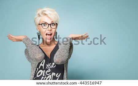 Fashionable blond girl in trendy clothes with short hair and blond hair in amazement spread her arms - stock photo