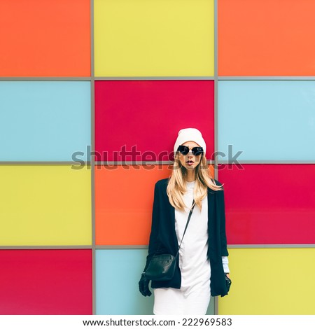 Fashionable blonde standing against a bright wall. Urban style - stock photo