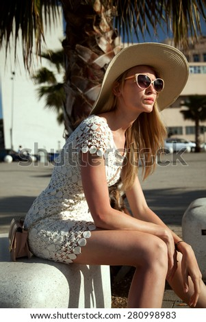 Fashionable blonde woman posing in sunglasses and hat. Sunny day. Vacation photo. - stock photo