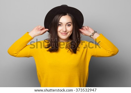 Fashionable brunette wearing bright yellow clothes holding her hat with eyes closed isolated on grey background - stock photo