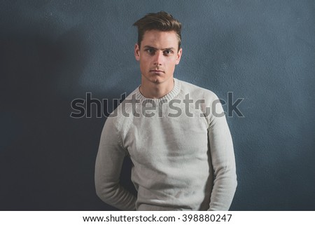 Fashionable casual young man wearing beige sweater. Standing against gray wall. - stock photo