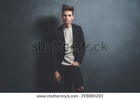 Fashionable casual young man wearing dark blue jacket and black jeans. Standing against gray wall. - stock photo