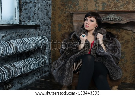 Fashionable caucasian woman in fur coat sitting by the window - stock photo