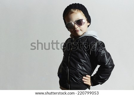 Fashionable child in sunglasses. Kid in Black cap.winter style.Posing Little boy.Children fashion - stock photo