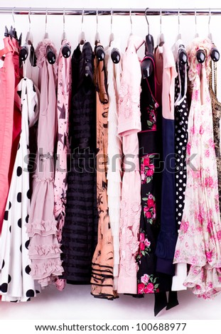 Fashionable clothes on pegs in a cloak-room - stock photo