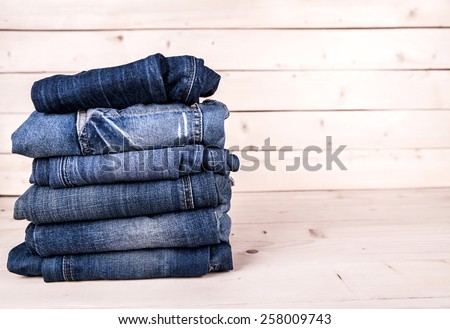fashionable clothes. pile of jeans on a wooden background - stock photo