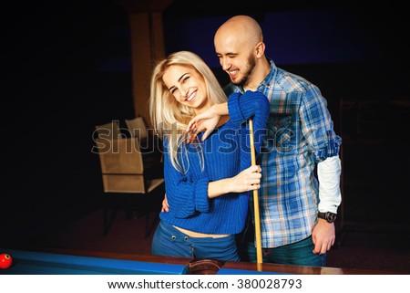 Fashionable couple having fun and plays billiard. American pool billiard. Billiard sport concept. Pool billiard game. - stock photo