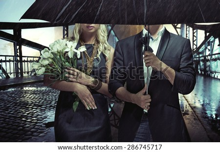 Fashionable couple on night city street - stock photo