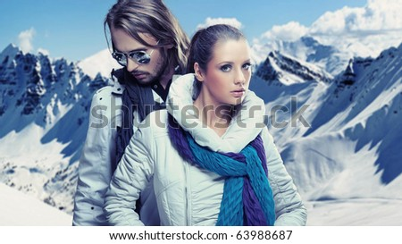 Fashionable couple over alpine mountains - stock photo