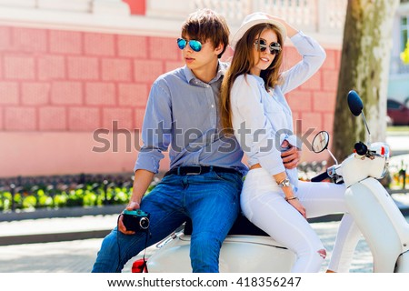Fashionable  couple posing  on the street, siting on scooter , wearing stylish casual clothes, bright sunglasses. Smiling  handsome guy and his pretty girlfriend hugging.  Man holding retro camera.  - stock photo