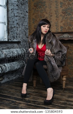 Fashionable dark-haired woman posing in a fur coat, vertical shot - stock photo