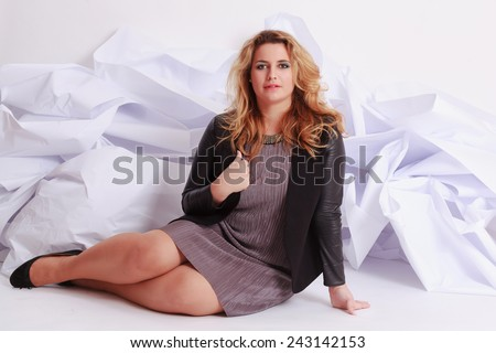 Fashionable, elegant woman with voluptuous curves in a gray dress, sitting in front of a white paper studio shot / Fashionable, elegant woman with voluptuous curves in a dress. - stock photo