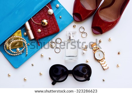 Fashionable female accessories watch sunglasses lipstick blue clutch and red shoes . Overhead of essentials for stylish young woman. - stock photo