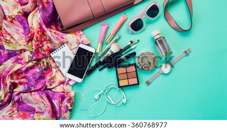 Fashionable female accessories watch sunglasses lipstick  pink  clutch and mobile phone. Overhead of essentials for stylish young woman. Different objects on blue  background . Bright summer colors.   - stock photo