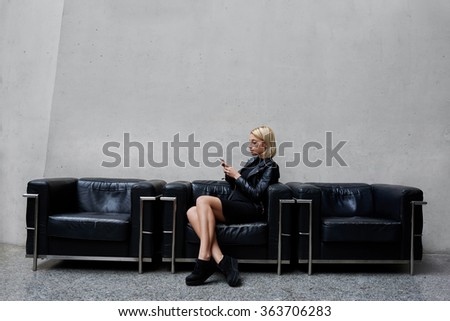 Fashionable female looking for a partner's number on mobile phone while waiting for him in modern studio,charming young woman chatting with her boyfriend on cell telephone during free time in work day - stock photo