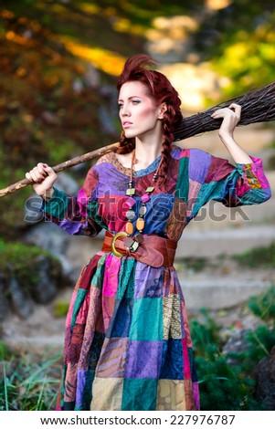 Fashionable girl holding broom - stock photo