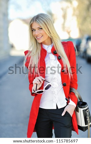 Fashionable girl in red dress with bag - stock photo