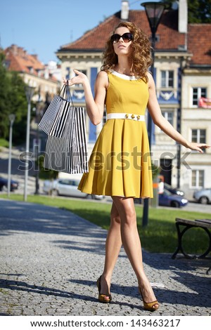 fashionable girl in yellow dress with shopping bag a old city street - stock photo