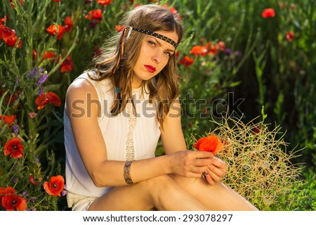 Fashionable girl sitting in the summer field - stock photo