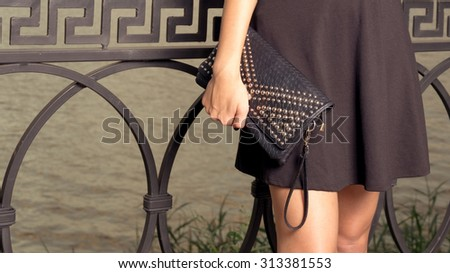 Fashionable girl with clutch standing near a fence close-up - stock photo