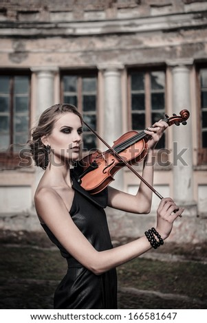 Fashionable gothic girl with violin - stock photo