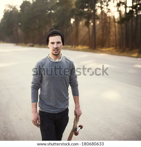 fashionable guy with skateboard - stock photo
