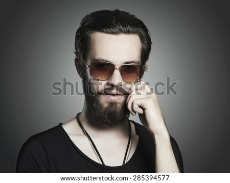 fashionable handsome man. Brutal bearded Sexy boy in trendy sunglasses - stock photo