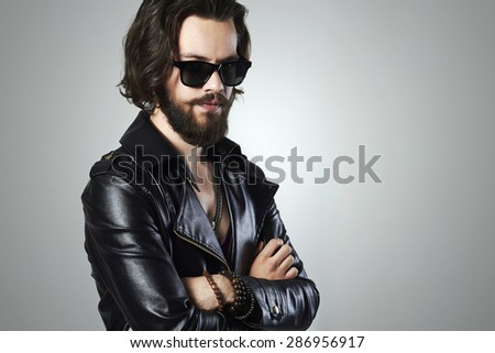 fashionable handsome man in a leather jacket. Brutal bearded Sexy boy in trendy sunglasses.rock and roll - stock photo