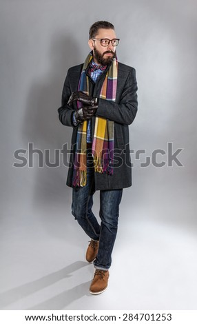 Fashionable handsome stylish bearded man in coat and in a checkered scarf and bow tie. - stock photo