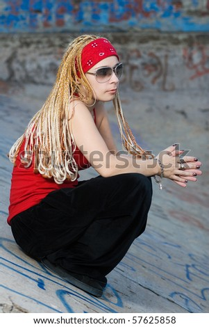 Fashionable hip-hop chick posing outdoors at graffiti sprayed wall - stock photo