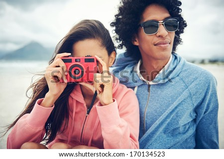 Fashionable hipster couple taking retro camera photo at beach - stock photo