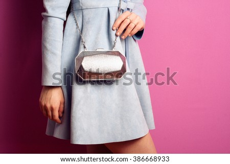 Fashionable lady in dress with silver small bag clutch near pink background - stock photo