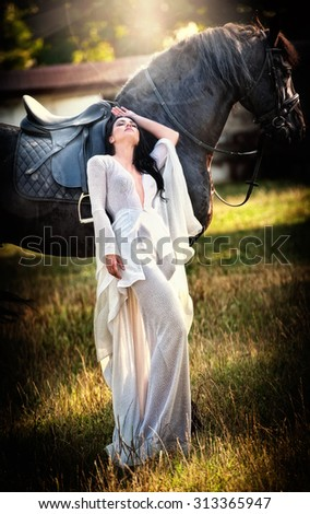 Fashionable lady with white bridal dress near brown horse in nature. Beautiful young woman in a long dress posing with a friendly black horse. Attractive elegant female with horse, sunny summer day - stock photo