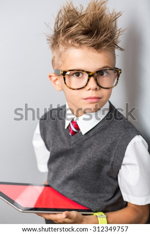Fashionable little boy in sunglasses and funny hairstyle using tablet with empty screen. Stylish kid in suit. Fashion children. Business boy - stock photo