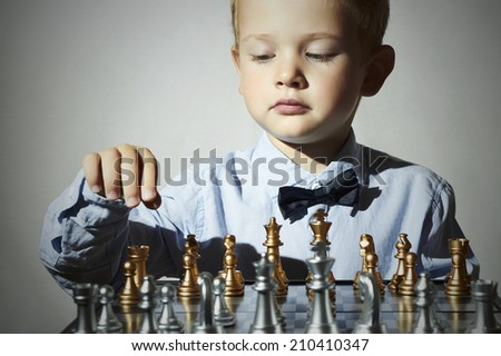 Fashionable Little boy playing chess.Smart kid.fashion children.5 Years Old Child in Bow-tie. Little genius Child. Intelligent game.Chessboard - stock photo
