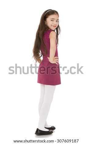 Fashionable little dark-haired girl in a stylish short dress is turned sideways to the camera . The girl smiles in her mouth not missing a few teeth-Isolated on white background - stock photo