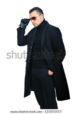 Fashionable man in black coat isolated over white background - stock photo