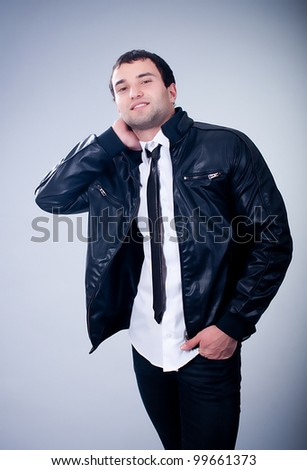 Fashionable man in jacket on gray background - stock photo