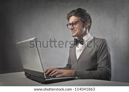 Fashionable man using a laptop computer - stock photo