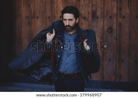 Fashionable mature male with beard holding coat on his shoulders while posing outdoors in autumn season, trendy adult hipster man dressed in modern clothes standing outside near brown wooden wall - stock photo