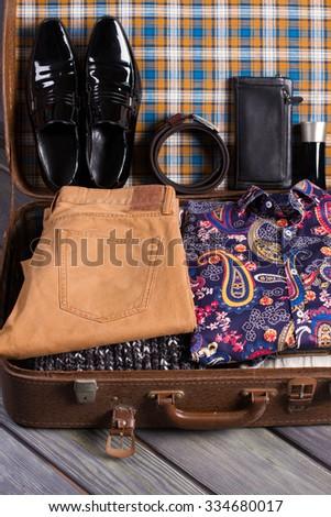 Fashionable men's clothing. Suitcase ready for travel. - stock photo