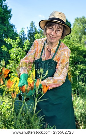 Fashionable middle-aged woman in a straw sunhat standing watering plants in a lush green garden with a happy smile as she leans towards the camera, close up view - stock photo