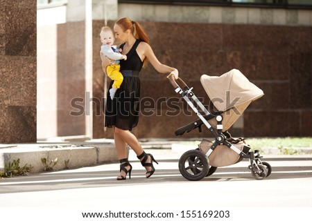 Fashionable modern mother on a city street with a pram. Young mother walks with a  child in the city. Beautiful young woman with a child in a baby carriage - stock photo