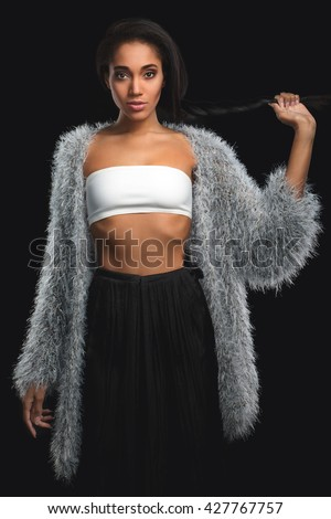 Fashionable mulatto in fur coat holding her braid hairstyle on black background. African American girl with long hair looking at camera - stock photo