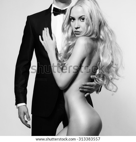 Fashionable photo of beautiful naked lady and man in suit - stock photo
