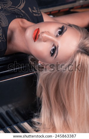 Fashionable portrait of blonde woman on piano looking at camera with brown eyes. Studio shot - stock photo