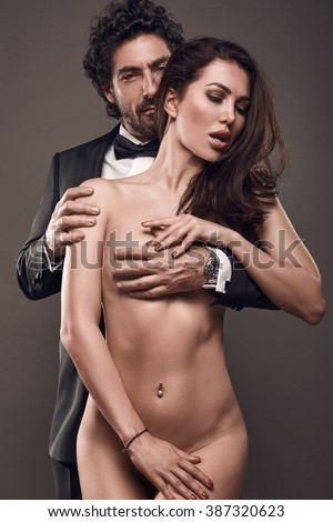 Fashionable portrait of elegant sexy couple in studio. Brutal man in suit hugging a naked woman from behind on dark background - stock photo