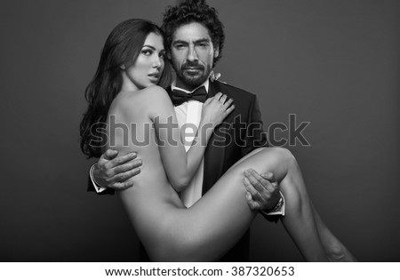 Fashionable portrait of elegant sexy couple in studio. Naked beautiful woman at the hands of a brutal man in suit on dark background. Grayscale - stock photo